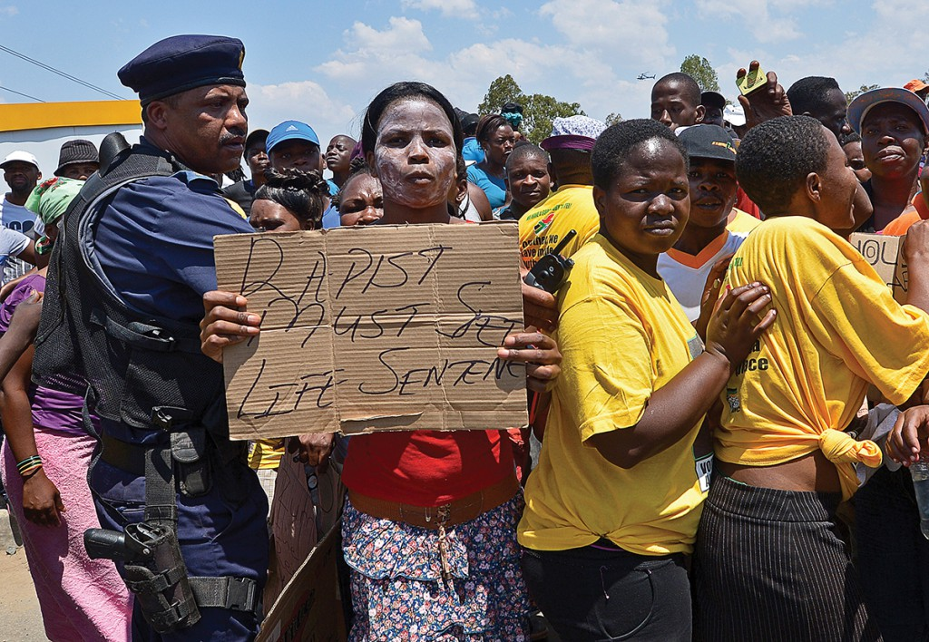 """A protester holds on October 18, 2013 a placard reading """"Rapist must get Life Sentence"""" during a demonstrating in Diepsloot, north of Johannesburg"""