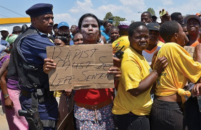"A protester holds on October 18, 2013 a placard reading ""Rapist must get Life Sentence"" during a demonstrating in Diepsloot, north of Johannesburg"