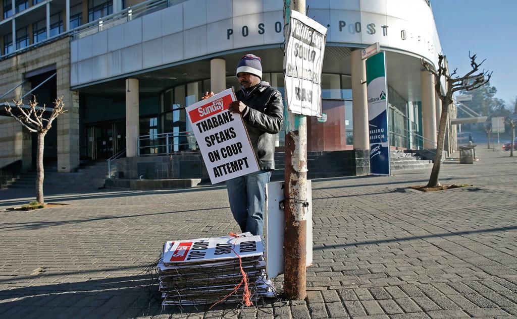 A worker hangs posters displaying newspaper headlines, in the capital Maseru