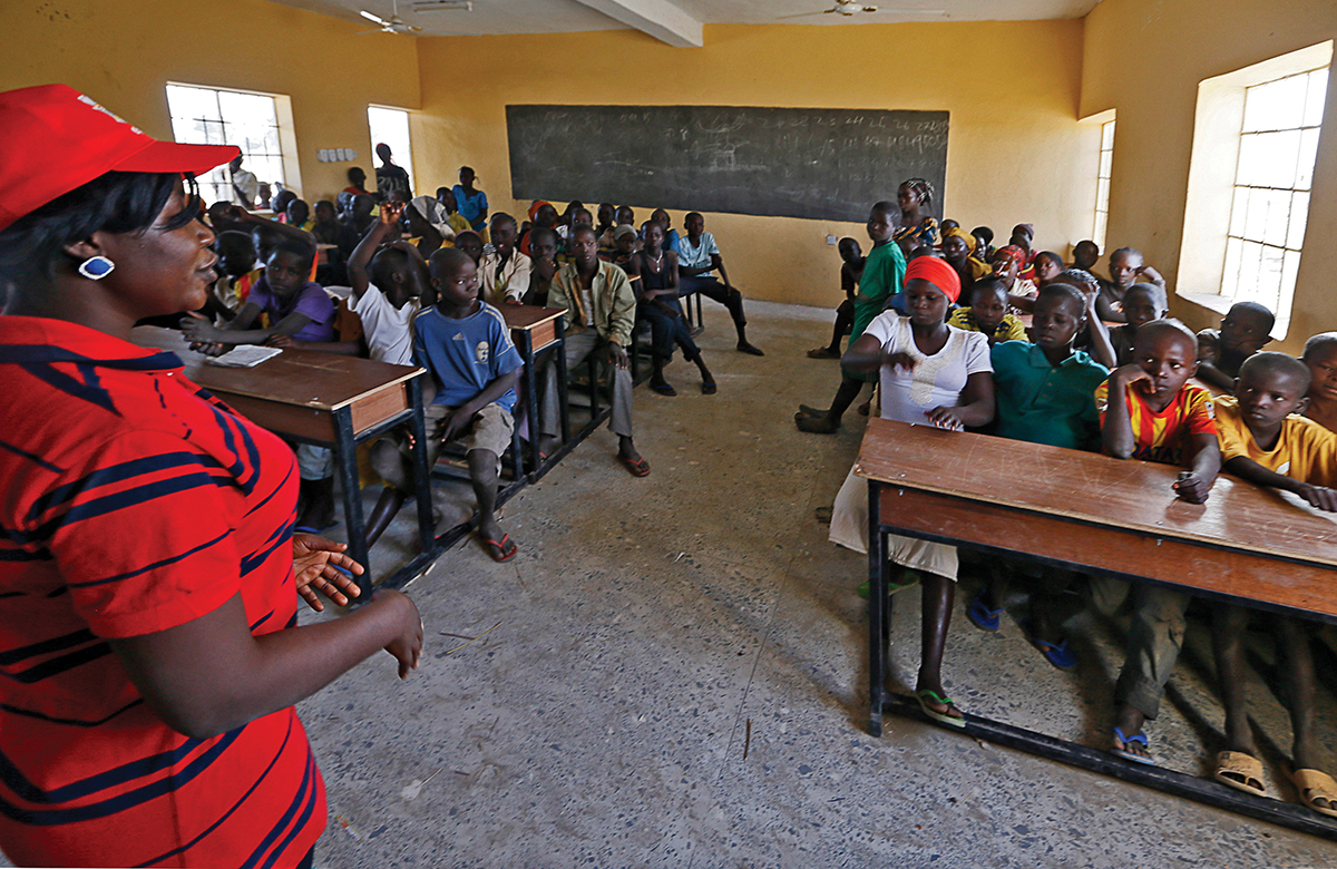 Children displaced as a result of Boko Haram attacks in the northeast region of Nigeria, attend class at Maikohi secondary school inside a IDP camp in Yola