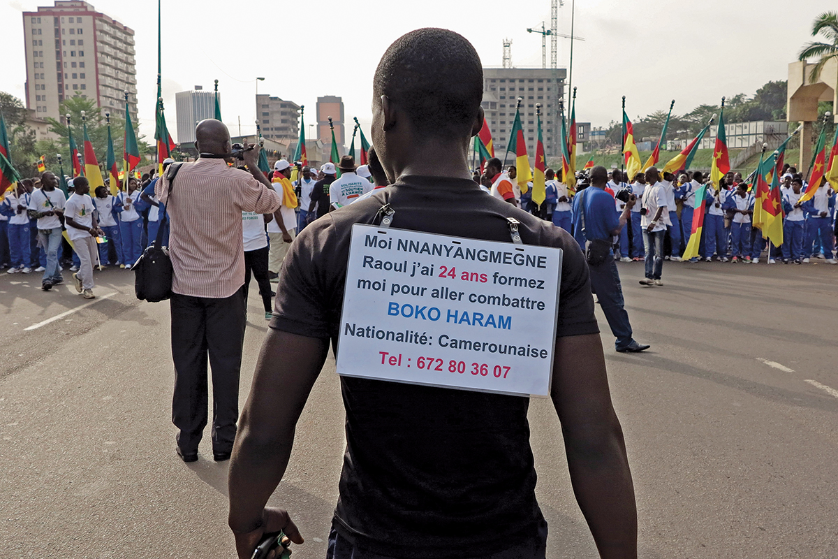 A man wears a sign on his back with his request to be trained and sent to the front line to fight against Boko Haram
